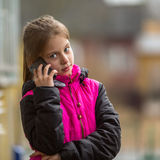 Ten-year girl talking on mobile outdoors. Communication Stock Image