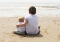 Ten year old with baby brother sitting on the beach Royalty Free Stock Photography