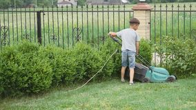 Ten year old boy mowing the lawn with a big lawn mower stock video