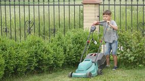 Ten year old boy mowing the lawn with a big lawn mower stock video footage
