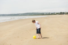 Ten year old boy playing football on the beach. In summer Royalty Free Stock Images
