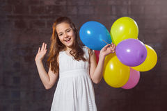 Ten year old caucasian girl with long hair posing in the studio with ballons Stock Photos