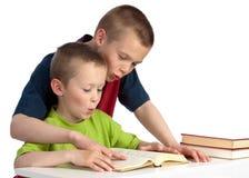 Ten-year-old che teching il suo fratello di bambino per leggere Immagine Stock Libera da Diritti
