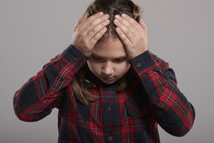 Ten year old girl holding head in frustration, waist up stock images