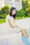Ten year old girl repaxing by  pool Stock Photos