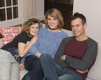 Ten year old girl sitting on couch with middle-aged parents Stock Images