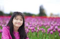Ten year old girl smiling in front of tulip fields Royalty Free Stock Image