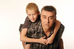Ten year old son cheerfully embraced his father sitting on his back. Isolated on white background Stock Photography