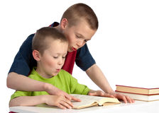 Ten-year-old teching his kid brother to read Royalty Free Stock Image