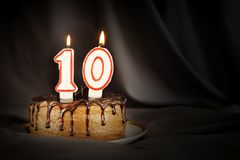 Ten years anniversary. Birthday chocolate cake with white burning candles in the form of number Ten. Dark background with black cloth stock photography
