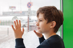 A ten years boy is  looking out of a window Stock Photos