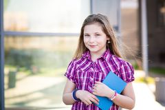 Ten years old blue eyed schoolgirl holding a book. Ten years old blue eyed schoolgirl standing and holding a book Royalty Free Stock Photo