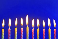 Ten yellow and pink burning birthday candles on blue stock image