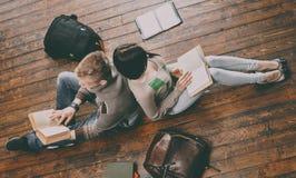 Tenagers que estudia en el piso en la universidad Fotos de archivo