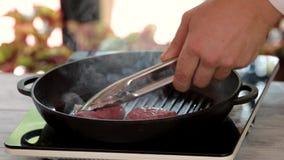 Tenaglie e pentola con le bistecche archivi video