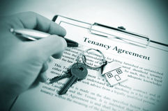 Tenancy agreement. Hand signing tenancy agreement on clipboard with keys and symbolic house keyring Stock Photo