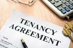 Tenancy agreement in a real estate agency. Tenancy agreement and keys from home in a real estate agency Stock Photo
