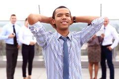 Tenant un comprimé, un jeune homme d'affaires noir bel est extérieur debout d'un bâtiment d'affaires, regardant avec confiance Photo stock