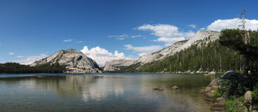 Tenaya Lake panorama. Panorama from the west end of Tenaya Lake in Yosemite National Park showing domes, clouds, and peaks Royalty Free Stock Image