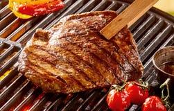 Tenazes de brasa de madeira que sustentam a carne na grade do BBQ fotografia de stock