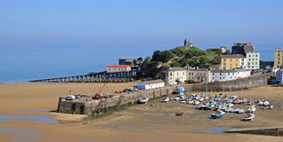 Tenby Harbour, with the tide out. A view of Tenby harbour, in south Wales, with colourful, pastel houses overlooking the beach and sea, with the tide out Stock Image