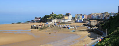 Tenby Harbour, with the tide out. A view of Tenby harbour, in south Wales, with colourful, pastel houses overlooking the beach and sea, with the tide out Stock Photos