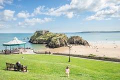 Tenby, Wales - Augustus 12, 2017: Mensen die van hun tijd bij Tenby-Kasteelruïnes en zandige strandmening genieten at low tide ti stock fotografie