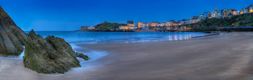 Tenby, Wales Harbor Evening Panorama. Lights and colorful buildings around beach of Tenby (Dinbych-y-Pysgod) in South West Wales Royalty Free Stock Photo