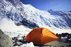 Tenda arancio al piede della montagna Immagine Stock