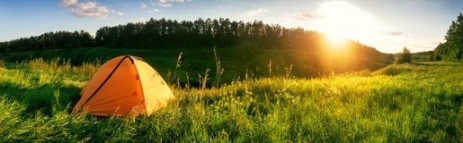 Tenda arancio nelle montagne su un prato verde immagini stock libere da diritti