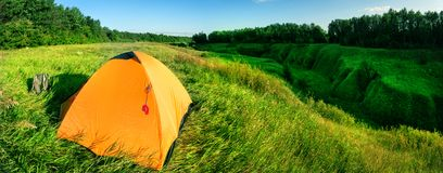 Tenda arancio su una collina verde sopra un burrone immagini stock libere da diritti