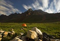 Tenda arancio sulle colline verdi delle alte montagne nella luce della luna Fotografie Stock