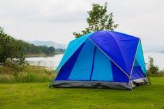 Tenda blu vicino al lago con la montagna, cielo, alberi nei rai Immagini Stock