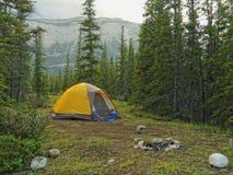 Tenda che si accampa nella foresta con il contesto della montagna Immagini Stock Libere da Diritti