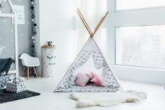 Tenda con i cuscini vicino alla finestra nello studio, stanza del ` s dei bambini, pelliccia del ` s dei bambini sul pavimento Fotografia Stock Libera da Diritti