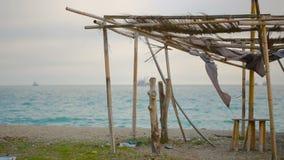 Tenda crollata di bambù su una spiaggia abbandonata Non la stagione, concetto di ecologia stock footage