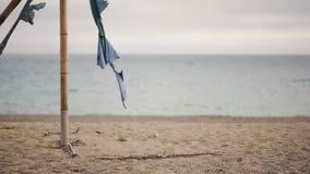 Tenda crollata di bambù su una spiaggia abbandonata Non la stagione, concetto di ecologia archivi video