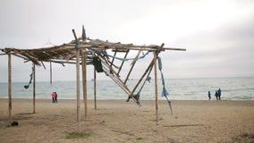 Tenda crollata di bambù su una spiaggia abbandonata Non la stagione, concetto di ecologia video d archivio