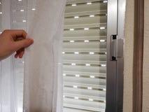 Tenda di finestra commovente dell'uomo, mostrante giù l'otturatore del rullo fotografie stock libere da diritti