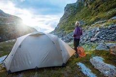 Tenda e donna turistiche nel tramonto Norvegia delle montagne fotografia stock libera da diritti