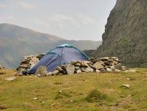 Tenda e protezione frangivento alpine dalle rocce Fotografia Stock