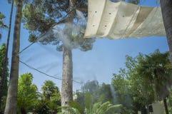 Tenda e spruzzatori che spruzzano acqua vaporizzata al parco pubblico Immagine Stock Libera da Diritti
