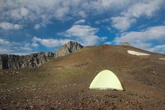 Tenda gialla in montagne sopra cielo blu fotografie stock libere da diritti