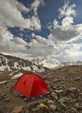 Tenda rossa in alte montagne al tramonto Immagine Stock