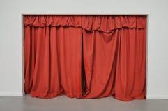 Tenda rossa chiusa sopra la grande entrata su una parete bianca immagini stock