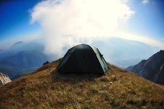 Tenda sul bordo della scogliera della montagna con l'attesa del cielo blu Fotografie Stock Libere da Diritti