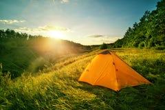 Tenda turistica arancio su una collina sopra il burrone immagine stock