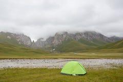 Tenda turistica nel campo del campo fra i montains Immagine Stock