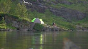 Tenda vicino al lago della montagna stock footage