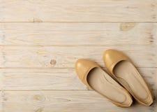 Tendance de mode - le ` s de femmes chausse la couleur d'or de perle sur un CCB en bois Image stock